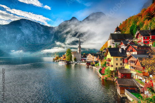 Fotografia  Foggy autumnal sunrise at famous Hallstatt lakeside town reflecting in Hallstatt