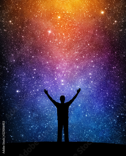Man silhouette on a night sky background with bright stars. Man watching the stars. Science, education and religion team concept background. Elements of this image furnished by NASA.