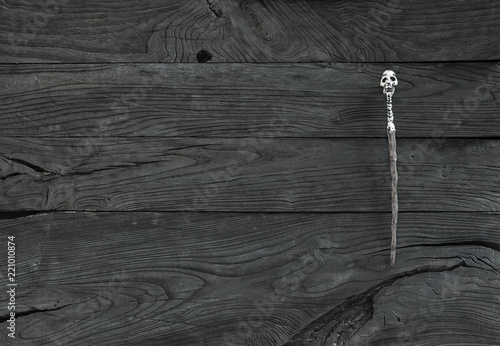 wand of a magician on a black wooden background