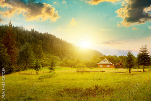 Canvas-taulu Small house on slope Carpathians at sunset.
