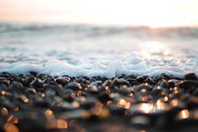 Small Sea Foam Waves Breaking On A Pebble Beach At Sunset