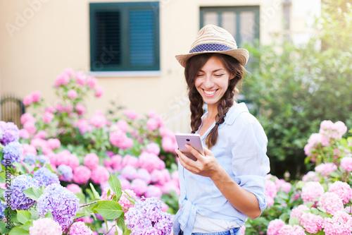 Happy girl is using smartphone Fototapet
