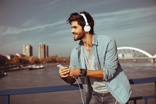 Young Man Listens To Music Via...