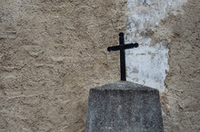 Black Metal Cross In Front Of A Grungy Wall On A Cemetery