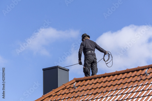 Tablou Canvas Chimney sweep cleaning a chimney standing on the house roof, lowering equipment