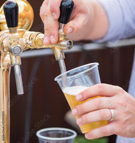 Tuinposter Bier / Cider A bartender serving beer at a dispenser in plastic glasses