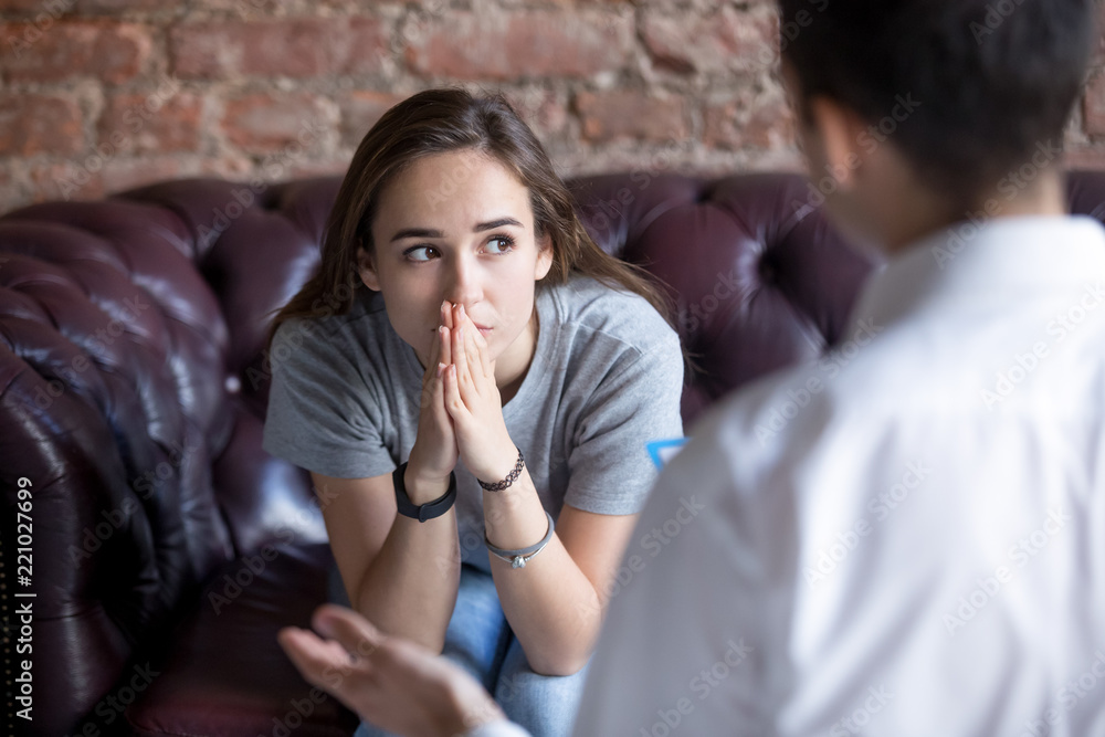 Fototapeta Young woman visiting therapist counselor. Girl feeling depressed, unhappy and hopeless, needs assistance. Serious disease, unwilling pregnancy, abort or death of loved one, addiction to drugs concept