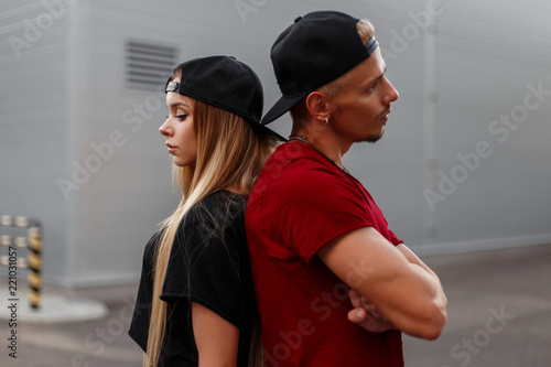 Fotografie, Obraz Beautiful stylish young couple in fashionable clothes with a cap stand back to b
