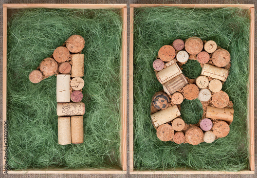 Photographie  Number 18 eighteen made of wine corks on green background in wooden box