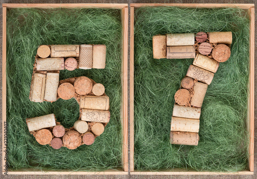 Fotografie, Obraz  Number 57 fifty seven made of wine corks on green background in wooden box