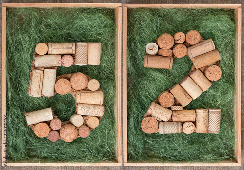 Fotografia  Number 52 fifty two  made of wine corks on green background in wooden box