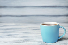 Blue Ceramic Cup With Hot Aromatic Coffee On Table
