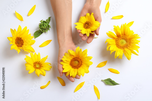 Woman holding beautiful sunflowers on white background, top view