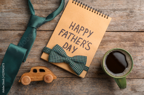 Flat lay composition with notebook, cup of coffee and accessories on wooden background. Father's day celebration