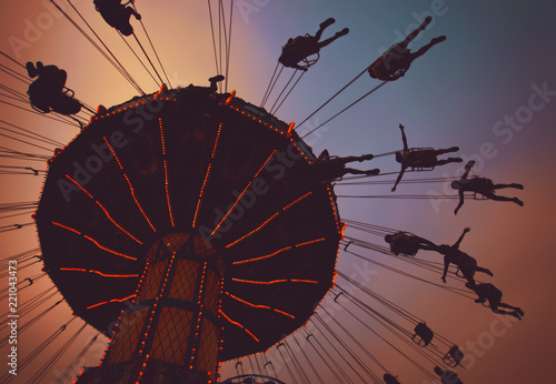 Fotografia beautiful fair sunset photo of a swing ride full of people in silhouette