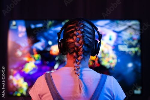 фотографія  A girl is a gamer or a streamer in front of a television playing