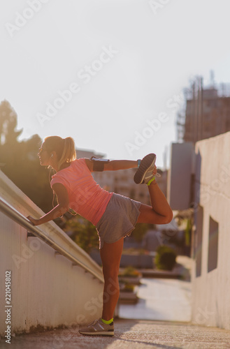 Young female runner stretching her leg after running. Stay fit concept urban.