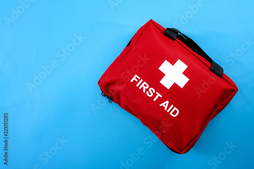 First aid treatment and medical emergency response concept with flat lay view of a red with a white cross first aid kit isolated on blue background with copy space for text