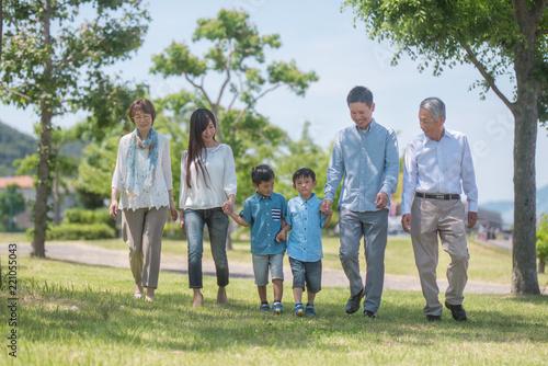 手を繋いで公園を歩く三世代家族