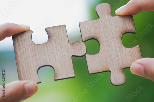 Valokuva  Two hands trying to connect couple puzzle piece with green background