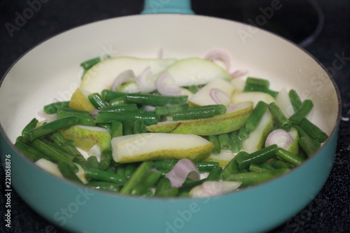 Fotografie, Obraz  Sliced pear, chopped broccoli, and sliced red onion in a pan