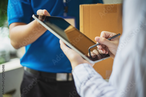 Woman appending signature sign on tablet after accepting receive boxes from deli Wallpaper Mural