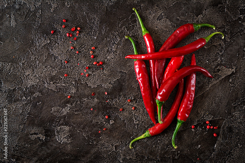 Photo Stands Hot chili peppers Red hot chili peppers on grey table. Top view