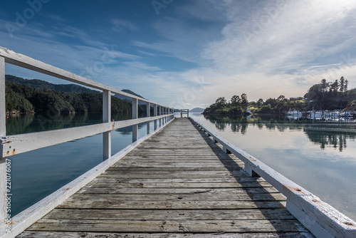 The wooden pier at Elaine Bay on a calm, sunny in the Marlborough Sounds, New Zealand.
