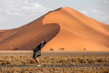 Young Male Traveler And Photographer Standing With Curve Shape In Namib Desert With Orange Sand Dune In The Background. Travel Namibia, Africa Concept