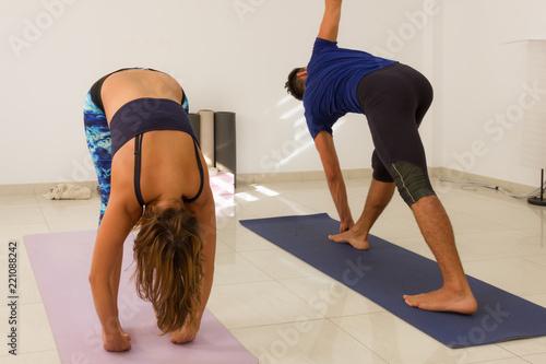Couple Of Students Practicing Ashtanga Yoga Mysore Style Individual Practice In Group Female Yogi In Padahastasana And Man In Parivrtta Trikonasana Standing Poses Healthy Exercise Concept Buy This Stock Photo And