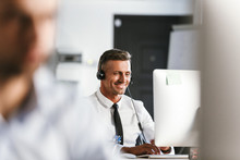 Photo Of Businesslike Man 30s Wearing Office Clothes And Headset, Smiling While Sitting By Computer In Call Center