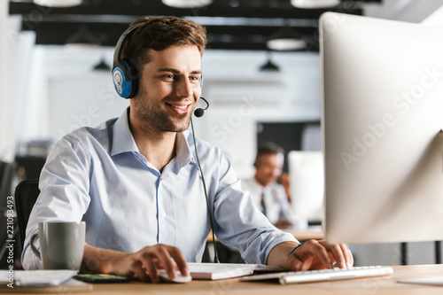 Carta da parati Photo of young worker man 20s wearing office clothes and headset, smiling and ta
