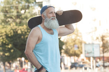 Happy Bearded Old Man. The Concept Of Life Satisfaction. Portrait Of A Positive Gray-haired Man With A Skateboard. Winner Concept.