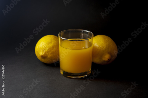Two lemons with glass of juice over black background.