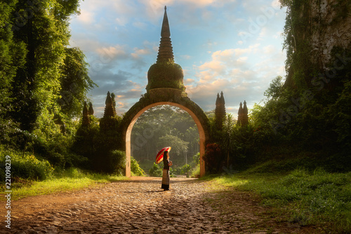 Fotobehang Bedehuis Lady hold red umbrellas with arch at Khao Na Nai Luang Dharma Park in Surat Thani Thailand