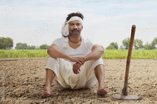 Farmer is sitting in field with hoe