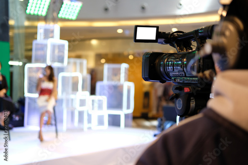 Tuinposter video production camera recording live event on stage. television social media broadcasting seminar conference.