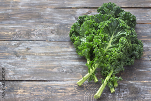 Fresh green curly kale leaves on a cutting board on a wooden table. selective focus. free space. rustic style. healthy vegetarian food