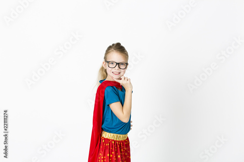 Photo  blond supergirl with glasses and red robe und blue shirt is posing in the studio
