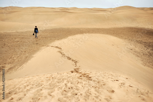 Mature female tourist walking barefoot on sand dune, rear view, Las Palmas, Gran Canaria, Canary Islands, Spain