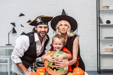 Portrait Of Happy Parents And Son In Halloween Costumes At Table With Pumpkins At Home