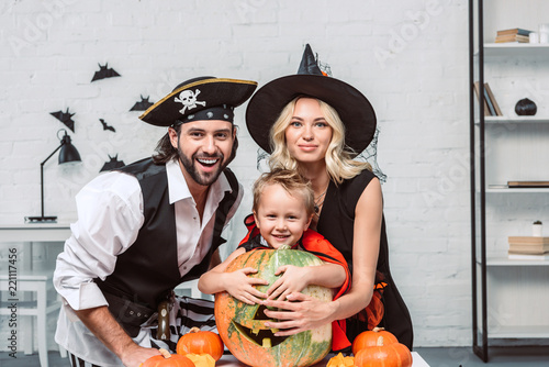 portrait of happy parents and son in halloween costumes at table with pumpkins a Tapéta, Fotótapéta