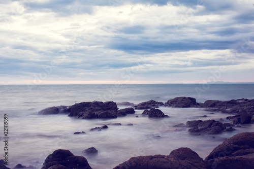 View of a rocky coast at the sunset. Dramatic sea view before rain
