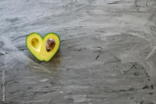 Heart-shaped avocado on grey background