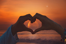 Silhouette Of Couple Making Heart - Shape Symbol With Moon Rising From Ocean / Sea Horizon.