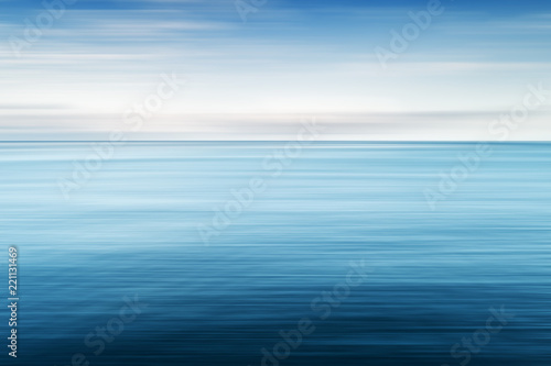 Photo sur Aluminium Piscine Abstract background of blue sea and cloudy sky over it. Motion blur sea water and sky with white clouds.