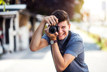 Young Male Tourist With Camera At City