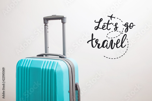 Photo Suitcase on the white background and inspirational travel quote.