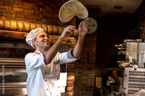 Keuken foto achterwand Pizzeria Skilled chef preparing dough for pizza rolling with hands and throwing up