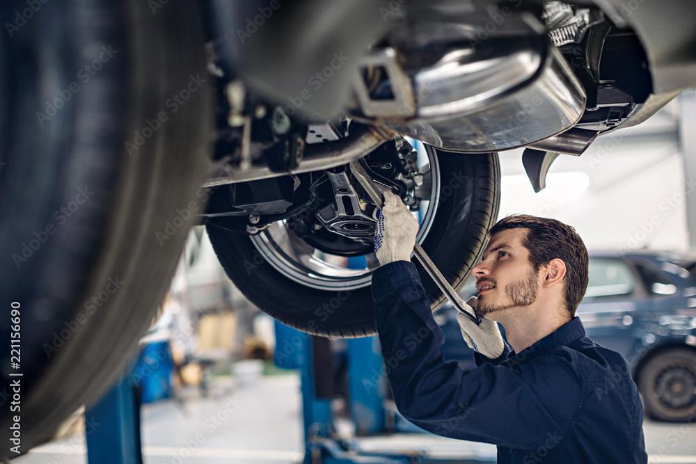 Fototapety, obrazy: Auto car repair service center. Mechanic examining car suspension
